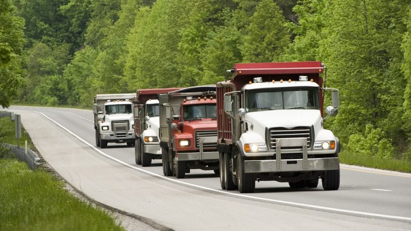 Heavy vehicles on a green highway.